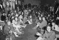 THE LIBERATION OF BERGEN-BELSEN CONCENTRATION CAMP, APRIL 1945  ~  Women and children crowded together in one of the camp huts. There is no furniture. Any spare clothing is hung on the walls.