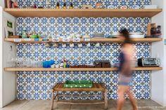 Cozinha tem parede revestida com ladrilho hidráulico com padronagem geométrica e prateleiras de madeira.