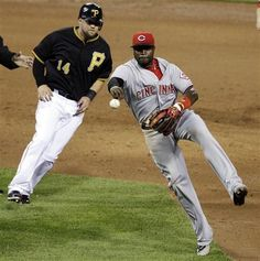 Cincinnati Reds second baseman Brandon Phillips, right, throws to first after tagging out Pittsburgh Pirates' Casey McGhee (14) to complete an inning-ending double play on Pirates' Jose Tabata during the fifth inning of a baseball game in Pittsburgh, Tuesday, May 29, 2012. The Reds won 8-1.