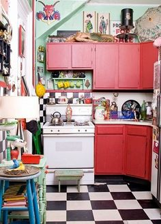 Wonderful kitchen, red cabinets, vintage stove, black and white floor, kitsch decor