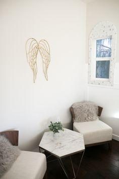 A room fit for an angel! This seating area with two lounge chairs and a hexagon marble table get a touch of ethereal whimsy with these handmade gold wings!