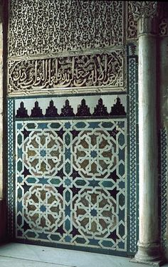 Image SPA 0706 featuring decorated area and column or pillar from the Alhambra, in Granada, Spain, showing Geometric PatternFloriated Arabesque and Calligraphy using ceramic tiles, mosaic or pottery and stucco or plasterwork.