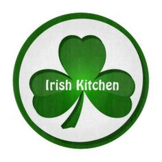 "A sweet glass cutting board featuring a large shamrock with a green border with customizable text across the shamrock which currently reads, ""Irish Kitchen""."