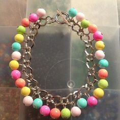Multiple colored glass beads on a chain bracelet.       8 inches with toggle clasp