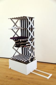 """by Kim Thome  """"The wardrobe is packed fully extended, then collapsed for your travels. When you reach your destination the wardrobe is opened and all your things are all visible and neatly organized making living out of a suitcase more enjoyable.  The main structure is aluminium and the linen fabric is stretched around lightweight frames.  The suitcase-wardrobe weighs less than 2kgs."""""""