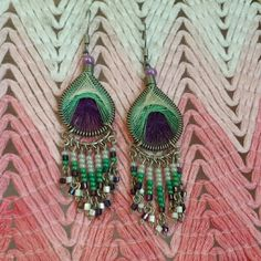 Peacock woven and beaded earrings Peacock earrings with woven center and beaded dangle. Best for casual wear! Make an offer! 25% off bundles of two or more items! Earthbound  Jewelry Earrings