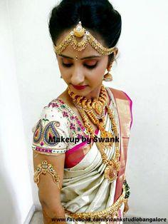 Traditional Southern Indian bride, Asha wears bridal silk saree and jewellery for her Muhurat. Makeup and hairstyle by Swank Studio. #BridalSareeBlouse #SariBlouseDesign #bridalgoldjewellery #maangtikka #statementnecklace  Silk kanchipuram sari. Tamil bride. Telugu bride. Kannada bride. Hindu bride. Malayalee bride  Find us at https://www.facebook.com/SwankStudioBangalore