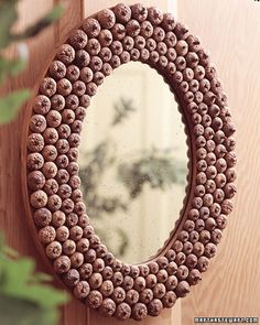 """A wide wooden frame, decorated with four rows of acorn caps in graduated sizes, becomes a perfect addition to your home during autumn."" http://www.marthastewart.com/275172/fall-harvest-decorating#"