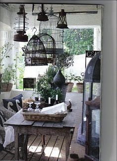 Porch with hanging birdcages and lanterns  I need to do something with the plethora of birdcages I collected during my shabby chic obsession phase