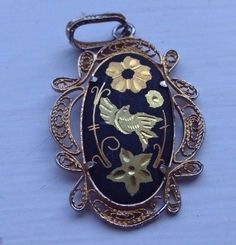 Vintage-Black-and-Gold-Coloured-Oval-Pendant-with-Flower-Design