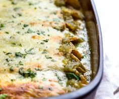 These Green Chile Chicken Enchiladas use shredded rotisserie chicken, white beans, corn and plenty of Pepper Jack cheese then are smothered in a green salsa verde. Super easy to put together and are great to freeze for later. www.keviniscooking.com