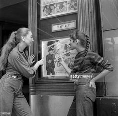 Two members of a teenage girl gang looking at a cinema poster starring one of their movie heroes