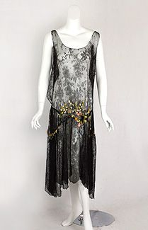 Circa 1925 Chantilly lace flapper dress with ribbon art flowers. While short skirts were widely accepted by the late 1920s, the mood of the design could vary widely: hard edged, geometric Deco; or a feminine lace creation as in this beauty. The skirt is draped longer and fuller on the sides. Bias-cut draping continues up to the shoulders in back, creating soft flounces.