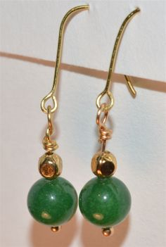 www.ETSY.com/shop/HarpersCauldron  Green Aventurine & Brass bead Earrings, on non-tarnish Brass Wire & non-tarnish Brass Fish Hooks - $ 5.  The deep green color of these 8 mm Aventurine beads is complemented by a small brass bead.  Green Aventurine is associated with the heart chakra. It is a stone of prosperity and wealth. It promotes a feeling of well-being and harmony.