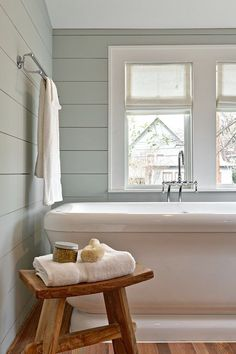 Restful bathroom with shiplap clad walls painted gray green, Benjamin Moore Tranquility, accented with a chrome towel rail over the foot of the pedestal tub with floor mount tub filler flanked by a rustic zen style stool adorned with a fresh white towel a