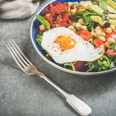 #Dieting concept breakfast  Healthy breakfast with fried egg chickpea sprouts seeds fresh vegetables and greens in bowls over grey concrete background selective focus square crop. Clean eating vegetarian food concept