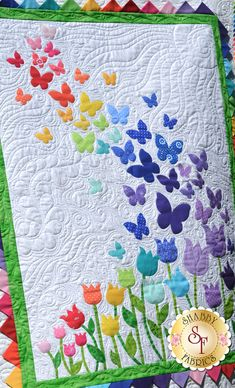 "Butterflies floating over a bed of tulips, finished with bright prairie points for the inner border. Finishes to 40½"" x 51½""."
