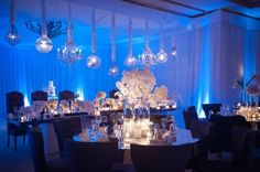 """""""A Good Affair Wedding and Event Production"""" - hard to tell because of the blue lighting, but interesting to use diff types of chandeliers, tons of flowers and candles (different sizes)"""