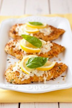 Parmesan crusted chicken with a garnish of cheese, lemon & basil
