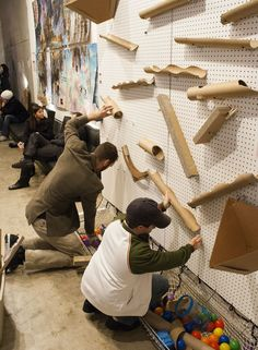 An oversized cross between pachinko and a marble run, this interactive installation invites people to place cardboard tubes of various length and diameter onto a grid of pegs protruding horizontally from a wall.