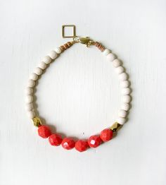 This is a vibrant pink coral and wood bracelet. It consists of six pink faceted glass beads, two faceted gold glass beads, many off white wooden