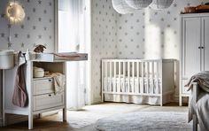Une table à langer et un lit dans une chambre de bébé grise et blanche au papier peint étoilé.