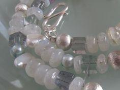 LUCIA  Mit der mittigen, facettierten Perle aus Muschelkern funkeln und schimmern um die Wette:   wunderschöne Rondelle aus echtem Mondstein,   fast völlig durchsichtige Würfel aus Fluorit in ganz zartem Hellgrün und Flieder,   riesige weiße Zuchtperlen und kleinere in Helltürkis   sowie sechs Kugeln aus 925 Silber.   Der sehr schön gearbeitete S-Verschluss schließt mit je einer liegenden Acht-   Symbol der Unendlichkeit.   Lucia heißt 'die Leuchtende' und bezeichnet eine Lichtgöttin.
