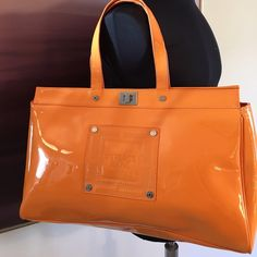 VERSACE PATENT LEATHER SHOULDER BAG 100% AUTHENTIC VERSACE JEANS COUTURE ORANGE PATENT LEATHER SHOULDER BAG.  AMAZING BAG NEVER USED FOR BOTH SPRING AND SUMMER.  THIS IS A STUNNING EYE CATCHER.  100 % AUTHENTIC.  COMES WITH DUST BAG.  THE BAG MEASURES 18 INCHES WIDE BU 11  INCHES TALL AND THE HANDLE HAS A 7 INCH DROP Versace Bags Shoulder Bags
