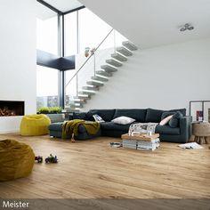 Eine offene Galerie mit einer freischwingenden Treppe bringt eine helle Atmosphäre ins Wohnzimmer. Vor dem modernen Kamin kann auf Sitzsäcken entspannt  …