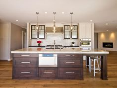 Glass pendant lights hang above the dark wood kitchen island in this kitchen space. The lights pair well with the glass front cabinets.