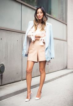 Aimee Song wears a blush pink ruffled blouse, shorts, a pastel blue blazer, a studded mini bag, and white pumps