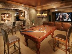 the ultimate man basement with a pool table, large theater center with leather, and a bar.