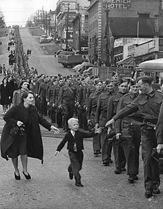 A child runs to a U.S. soldier as they march to the locomotives to take them to the boot camps to train them in the art of war. Its an emotionally appealing image: a child running to his father before he goes to war. The real power lies in the stream of men wearing the exact same uniform heading in a single direction.The child does not realize it, but the mother behind him tries to grab the child to prevent interference.