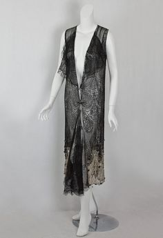 Beaded Chantilly lace flapper dress, c.1928 - This alluring dress is constructed from Black Chantilly lace with a wide hem border of bronze metallic lace, embellished with large crystals, black beads, silver beads, and rhinestones. The slightly uneven hem is charming artistic touch.