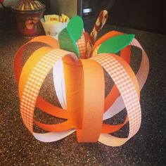 Pumpkin made with scrapbook paper and a painted toilet paper tube. Easy craft for kids!