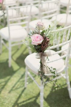 Flower arrangements on the aisle chairs - Image by Craig & Eva Sanders Photography - Bride in a Bespoke Gown with Gold Christian Louboutin Shoes, for an outdoor humanist ceremony in Wales with pastel colour scheme & copper hints.
