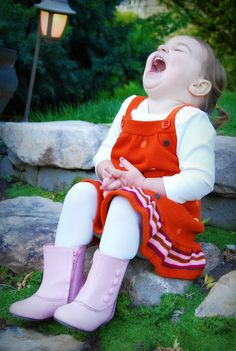 Little girl in red, white and pink sitting on stone steps laughing, laughter, joy, happy child