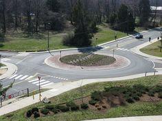 【ラウンドアバウト( roundabout)】信号機がない円形交差点の一種。3本以上の道路が接続されている交差点の中央に円形のスペースを設けたもので、車両はこの円形地帯に沿った環状道を時計回り(右側通行の場合は反時計回り)に一方通行で走行する。環状道を走る車両に優先権があり、進入する車両は必ず一時停止をしなくてはならない。一時停止した後に環状道を走ることで車両の走行速度を抑え、事故を抑制することができるうえ、信号機の維持費や電気代がかからず、災害時に停電しても交差点の機能が失われないなどのメリットがある。主に欧米諸国で普及が進んでおり、 円形地帯に凱旋門があるフランス・パリのシャルル・ド・ゴール広場が有名