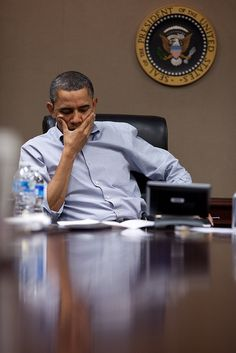 """""""More often than not, the President is in the office on most Saturdays to convene a national security or economic meeting. Here, on a Saturday in March, the President listens during a conference call on Libya in the Situation Room of the White House."""" (Official White House Photo by Pete Souza)"""