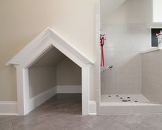 This laundry room features a tile dog shower and dog house. The pet shower doubles as a mud room feature. The opposite wall is painted in a black chalkboard