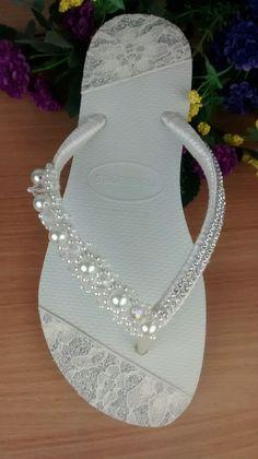 Legítima Havaiana Slim branca customizada com detalhes em lonita rendada na sola, bordado de pérolas com cristais e manta de strass na tira encapada com fita de cetim para dar o toque final e calcanhar de pérolas. Tamanhos disponíveis: 33/34 35/36 37/38 39/40 41/42 Uma ótima opção para qu... Bling Flip Flops, Wedding Flip Flops, Flip Flop Sandals, Wedding Shoes Bride, Bridal Shoes, Flip Flop Craft, Decorating Flip Flops, Bling Shoes, Bare Foot Sandals