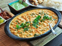 chickpea, coconut and cashew curry: recipe for spice mix (or use garam masala or curry powder), oil, onion, garlic, chili, cayenne pepper, cashews, coconut milk, chickpeas, spinach, salt, limes, cilantro