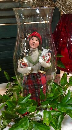 A creative way to display one of your favorite collectibles is inside a glass hurricane surrounded by fresh smilax, mini Christmas balls, and a dusting of snow.