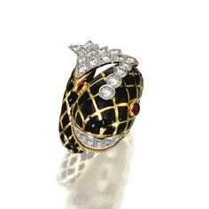 BLACK ENAMEL, DIAMOND AND RUBY FISH RING, DAVID WEBB The coiling fish applied with black enamel in a lattice motif, the eyes set with cabochon rubies, the mouth, head and tail set with round diamonds weighing approximately 2.00 carats, mounted in 18 karat gold and platinum, size 7½, signed Webb, one diamond missing. With signed box.