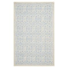 This hand-tufted wool rug's light blue hue and medallion motif make a lovely addition to your living room or master suite.  Product:...
