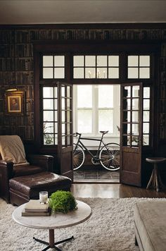 It looks like these doors lead to an enclosed porch.  Loved the paned glass in the doors themselves and in the transoms.  But it's the bookshelves all around the doorway that held my attention - my dream den or library would look just like this.