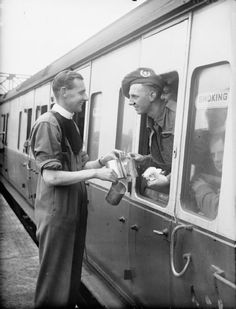 A British Army padre serves tea to a member of the Cameronians (Scottish Rifles) on a train at Headcorn station in Kent, 1 June 1940.