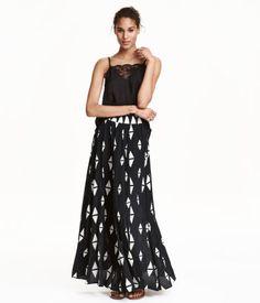 Zwart/wit. Een lange, uitlopende rok van geweven kwaliteit met een geprint dessin. De rok heeft elastiek in de taille. Ongevoerd.