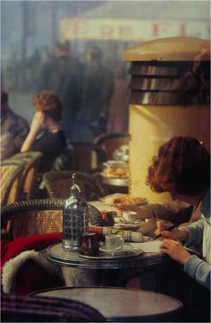 Saul Leiter : PARIS – LES DEUX MAGOTS – 1959. We can see on the top right of the photo, the photographer's ghostly shadow.