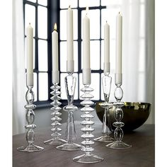 Shop numi taper candle holders.   Delicately handblown and heat-tempered strong in clear chem lab beaker glass.  Sculptural stacked discs ascend candlelight as modern heirlooms in three light-as-a-feather styles.